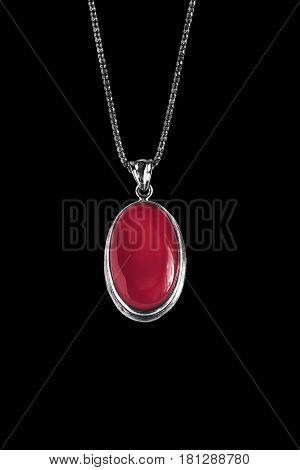 Red ruby medallion on silver chain isolated over black