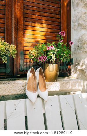 White bride's shoes on a white bench and flowers in the background.