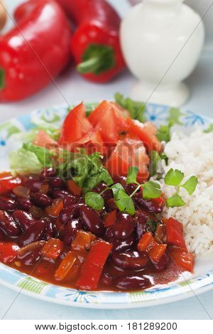 Red kidney beans served with cooked rice and tomato salad