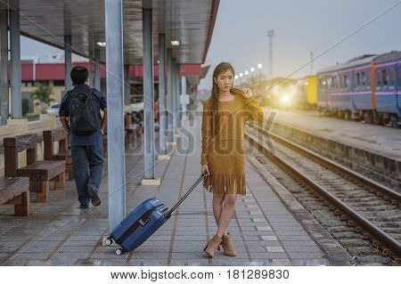 Petty girl waiting at the railway station with a suitcasetrain station with a train about to leave while the next train waits to come in.