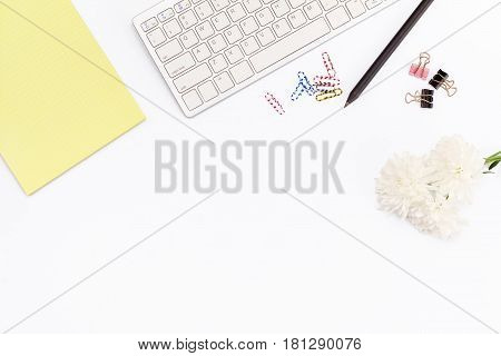 Yellow Legal Pad, Keyboard, Paper Clips, A Pencil And A Chrysanthemum Flower On A White Background.