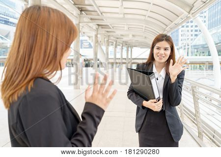 Young businesswoman say hello while holding a file - business concept