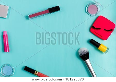 Beauty products, everyday make-up vibrant background. Cosmetic essentials - eyelashes, eyeshadow, lipstick and nail polish on blue, flat lay, top view