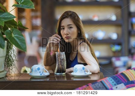Young woman serving table with happy adults in restaurant.