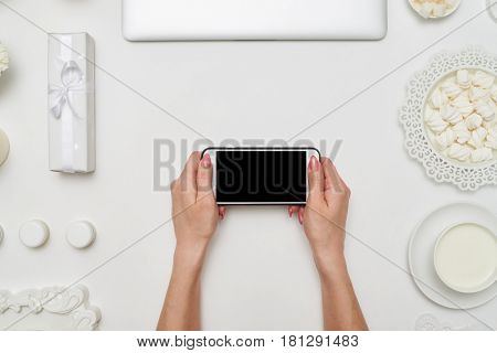 Overhead shot of hands of female holding horizontally cellphone with black screen on white background. Feminine workspace