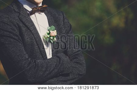 Wedding suit and accessories. Groom in outfit - shirt, bow-tie and jacket with floral buttonhole standing in the garden, close-up, crop, outdoors