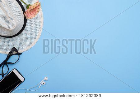 Top view of feminine accessories with telephone on a blue desktop. Glasses, headphones, flower over blue desktop
