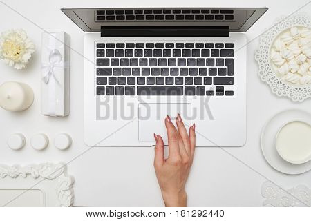 Overhead shot of a female hand using touchpad. Business concept, high angle. Desktop with accessories arrangement in white color flat lay shot