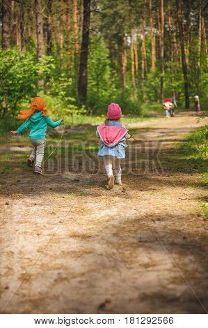 Group of little kids running in the forest. Middle spring green pine forest hike in Waldorf kindergarten.