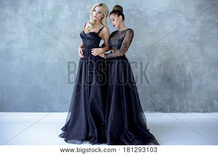 Beauty brides in bridal gown with lace veil indoors. Beautiful models girl in a black wedding dress. Female portraits of cute ladies. Women with hairstyle