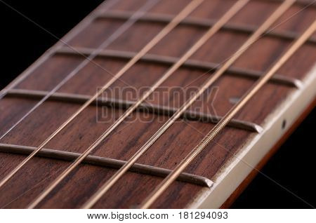 A piece of fretboard with frets and six strings of classical acoustic guitar