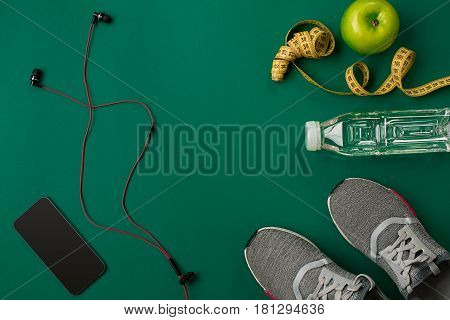Athlete's set with female clothing and bottle of water on green background. Top view. Still life. Copy space