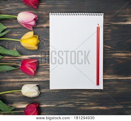 Notebook with Wishlist word on wooden background with spring flowers Tulips. Woman's wishlist concept. Close up