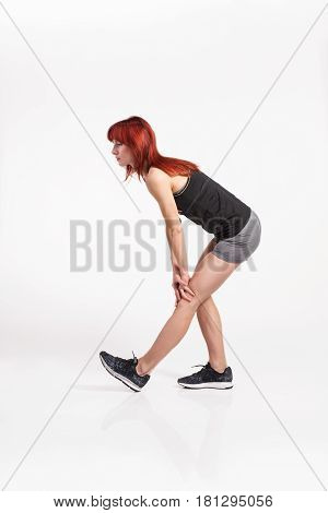 Attractive young fitness woman in black tank top and shorts stretching her legs. Studio shot on gray background.
