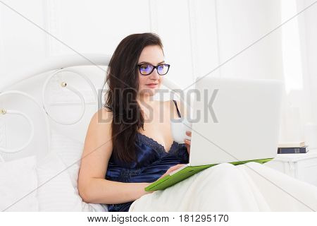 Morning coffee. Middle aged woman with laptop in bed. Beautiful woman in blue nightwear surfing internet at her computer. High key.