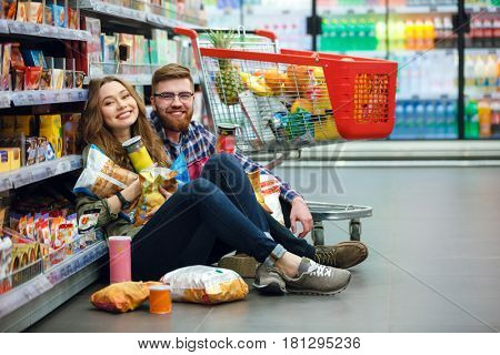 Young woman with big amount of packs and her man sitting on the floor of the mall eating chips
