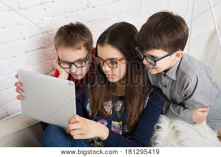 Group of kids in eye glasses look into tablet. Children computer games, social networks and media addiction concept. Girl and boys with tablet. Communication technologies.