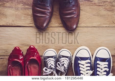 Father's shoes Placed in front of mother's shoes with baby on wooden floor - Concept of family leader.