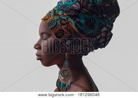 Young beautiful African woman in traditional style with scarf earrings crying isolated on gray background. racism depression or loneliness concept.