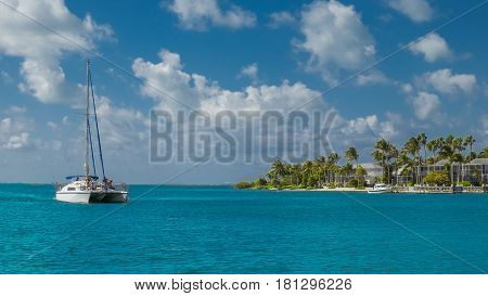 Catamaran on the Caribbean sea with Kaibo Crescent beach and Building in the background,Cayman Islands