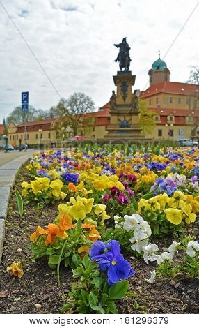 Closeup view on flowerbed on central square of Czech spa city Podebrady, which is dominated statue of George of Podiebrad, was King of Bohemia, and castle