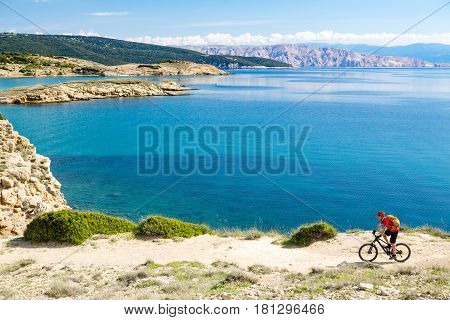Mountain biker riding on bike in summer or autumn inspirational mountains landscape. Man cycling MTB on enduro trail track at seaside and rocky dirt path. Sport fitness motivation and inspiration.