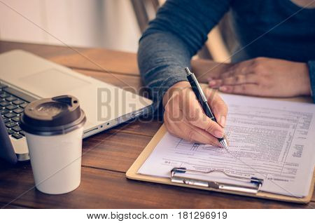 Businessman holding paperwork on the table and analyzing investment chart working in office. Business work concept.