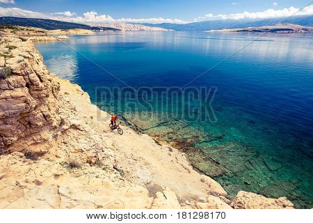 Mountain biker riding on bike in summer inspirational mountains and sea landscape. Man cycling MTB on enduro trail track at seaside and rocky dirt path. Sport fitness motivation and inspiration.
