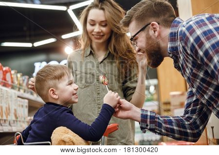 Side view of a bearded father in eyeglasses giving a candy to his son which sitting in shopping trolley in supermarket while mother standing near them