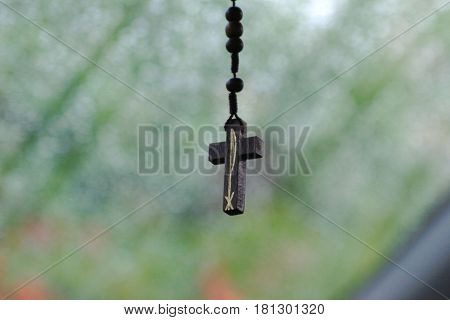 Wooden rosary beads and cross Wooden rosary beads and cross hang from a necklace