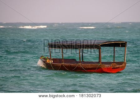 Scenic view of ocean shore and fisherman boat during low tide on island Zanzibar, Tanzania