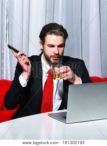 bearded man businessman long beard brutal caucasian hipster with moustache holding glass with whiskey has serious face unshaven guy with stylish hair in suit and red tie works at laptop computer