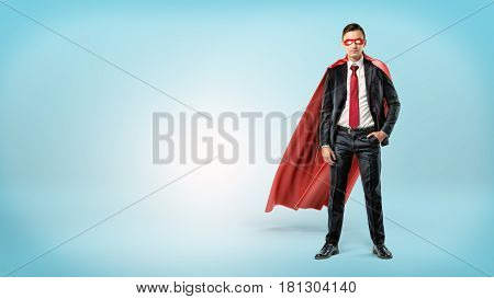 A self-assured businessman in a red cape and a mask standing with a hand in his pocket on blue background. Confidence and self-worth. Motivated employees. Business and work.