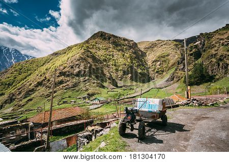 Stepantsminda Gergeti, Georgia - May 23, 2016: Small Old Self-made Two-wheel Tractor Or Walking Tractor French With Trailer Used In A Rural Household. Tractor On Road In Village