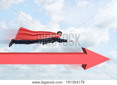 A businessman in a superhero cape flying straight through the clouds with a red arrow below him pointing forward. Business goals. Impossible made real. Risk and success.