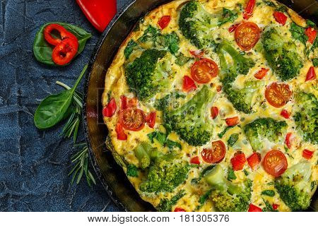 Frittata with broccoli spinach sweet peppers and tomatoes in iron skillet. Kind of Italian omelette with vegetables.