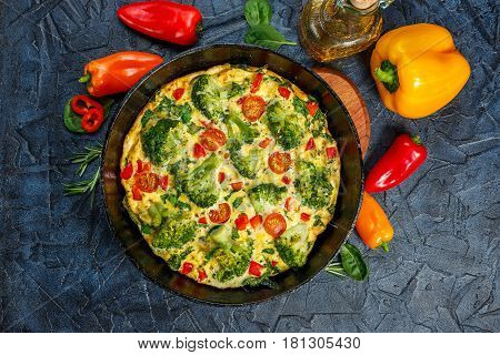 Frittata with broccoli spinach sweet peppers and tomatoes in iron skillet. Kind of Italian omelette with vegetables. Top view