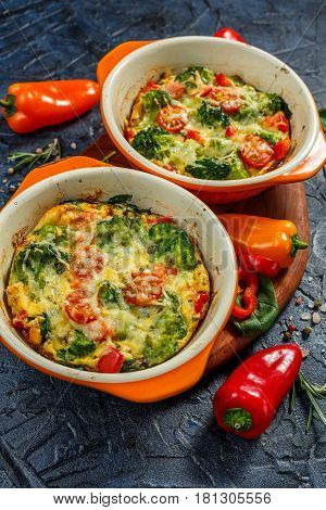Frittata with broccoli spinach sweet peppers and tomatoes in two ceramic forms for baking. Italian omelet with vegetables.