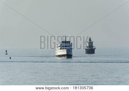 New Bedford Massachusetts USA - April 12 2017: Block Island ferry M.V. Carol Jean passing Butlers Flat lighthouse in New Bedford harbor on hazy morning