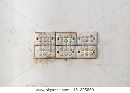Row of Dirty Light Switches on Stained Concrete Wall