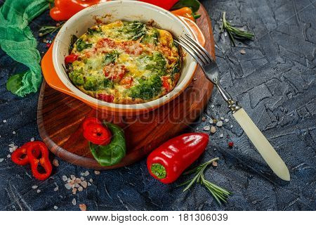 Frittata with broccoli spinach sweet peppers and tomatoes in ceramic baking dish. Italian omelet with vegetables.