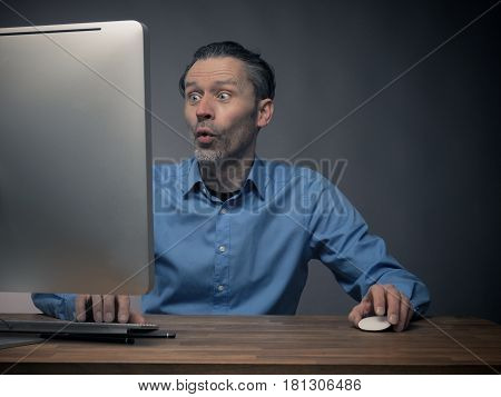 Handsome business man working on an office table with a computer