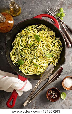 Cooked spiralized zucchini noodles in a cast iron pan overhead view, low carb dish