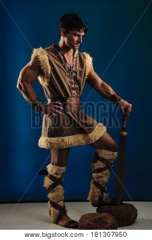 The muscular caveman is holding a sword.