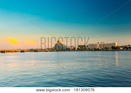 Riga, Latvia - July 1, 2016: Daugava River, National Library Building Castle Of Light And Hotel Radisson Blu At Scenic Embankment Pier Under Blue Sky At  Sunset Evening Time.