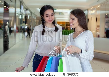 Two Cute Girl Walks In The Mall With Gift Bags Looking Into. Surprise From What He Saw. After Shoppi