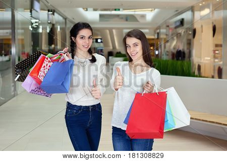 Two Cute Girl Walks In The Mall With Gift Bags, Showing Thumbs-up.