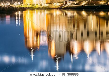 Mir, Belarus. Mir Castle Complex In Bright Evening Illumination With Glow Reflections On Lake Water. Famous Landmark, Ancient Gothic Monument Of Feudalism Under Blue Sky. UNESCO Heritage
