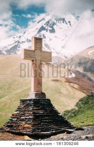 Cross On A Pyramid Of Stones On Kazbek Mount Background. Gergeti Trinity Church Or Tsminda Sameba. Holy Trinity Church Near Village Of Gergeti In Georgia. Spring Or Summer Season.