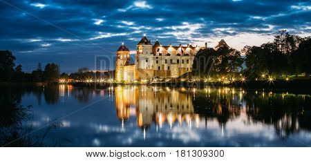 Mir, Belarus. Panorama Of Mir Castle Complex In Bright Evening Illumination With Glow Reflections On Lake Water. Famous Landmark, Ancient Gothic Monument Of Feudalism Under Blue Sky. UNESCO Heritage